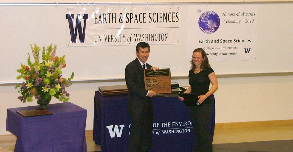 Photo of Brittany Brand receiving the Bassett Faculty Teaching Excellence Award from Robert Winglee.