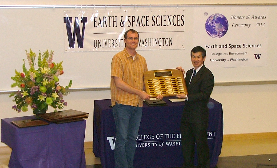 Photo of Isaac Larsen receiving the Johnston Prize for Research Excellence from Robert Winglee.
