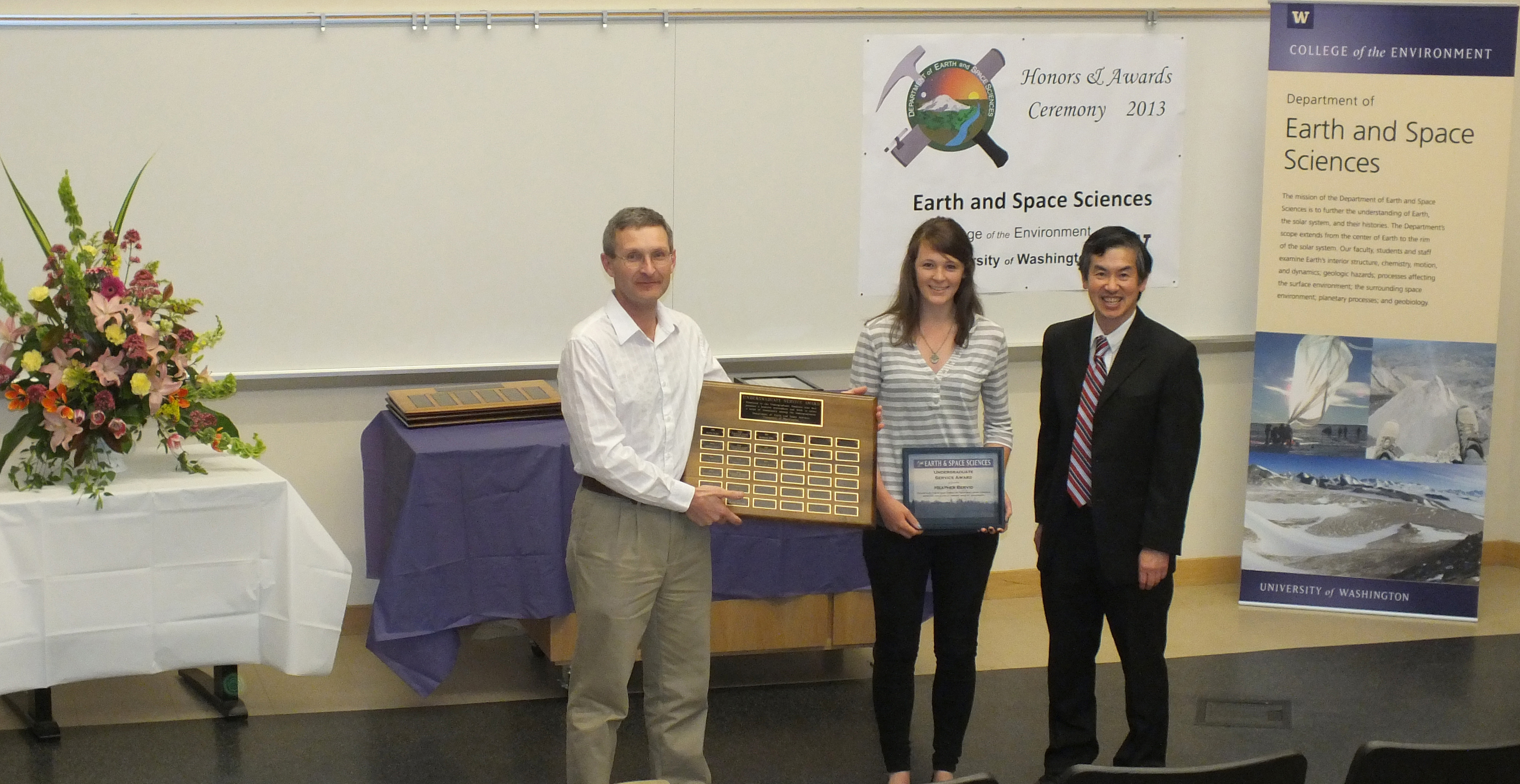 Photo of Heather Bervid receiving the Undergrad Service Award from John Stone and Robert Winglee.