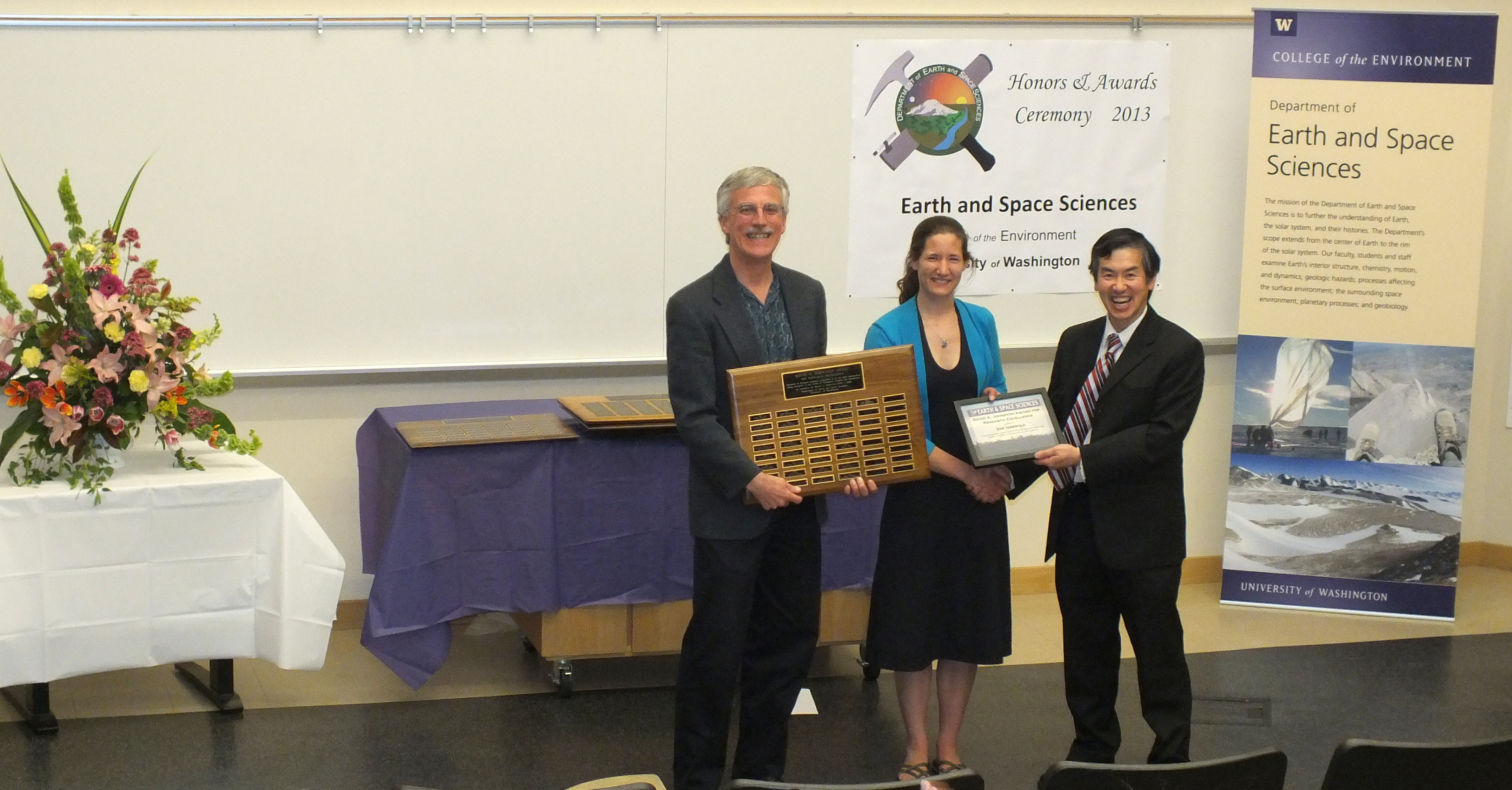 Photo of Zoe Harrold receiving the Johnston Prize for Research Excellence from Ken Creager and Robert Winglee.