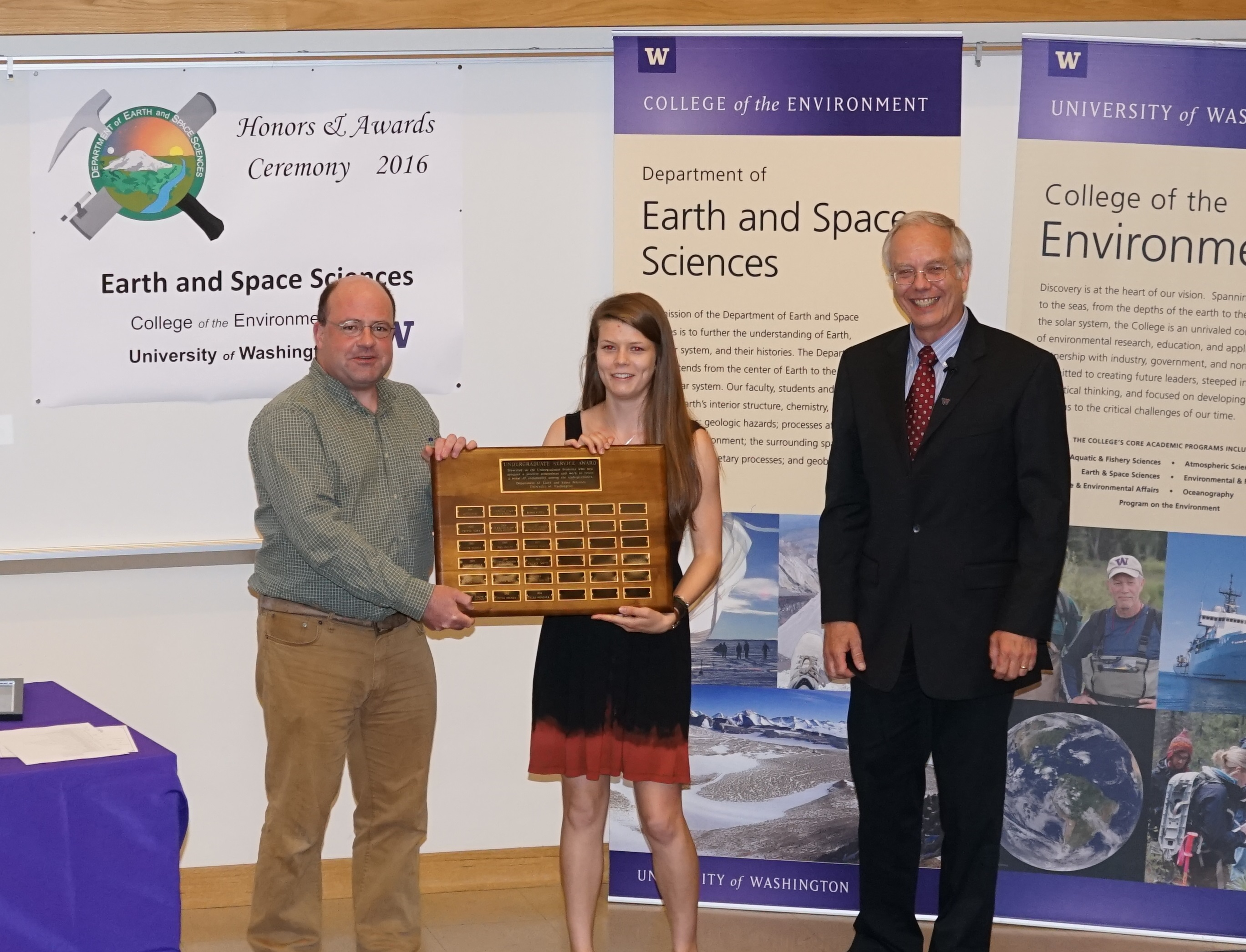 Photo of Cleo Woodcock receiving the Undergrad Service Award from Gerard Roe and Bruce Nelson.